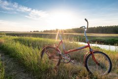 Bicycle in the field near the river. Royalty Free Stock Images