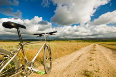 Bicycle on a field with road Stock Photo