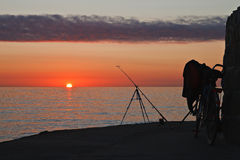 Bicycle and fishing rod. Mole in Warnemuende (Baltic Sea) in sunset light Stock Photo