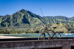 Bicycle and fishing rod, Hanalei Bay, Kauai. A vintage bike and fishing rod resting on the pier at Hanalei Bay, Kauai, Hawaii, with lush mountains on a sunny day Royalty Free Stock Photos