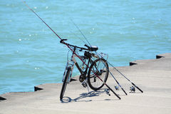 Bicycle and Fishing rods. On the sunshine day Royalty Free Stock Photos