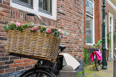 Bicycle with flower decorated wicker basket near the brick house Royalty Free Stock Images