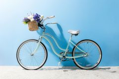 Bicycle with flowers. Side view of bicycle with flowers in basket in front of blue wall stock images