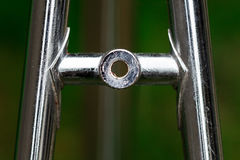 Bicycle frame part, detail from top stay, brake holder made of s. Ilver chromed metal pipe tubes on a blur green background Royalty Free Stock Photo