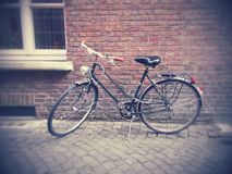 Bicycle in front of a brick wall. Stock Photo