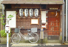A bicycle in front of a Japanese restaurant with lanterns in Tokyo. A white bicycle in front of a wooden storefront with Japanese lanterns on the street in Stock Photos