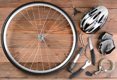 Bicycle Gear. Overhead view of bicycle gear laid out on a rustic wooden floor. Items include, Wheel, pump, gloves, tools, helmet and lock. Horizontal format Royalty Free Stock Photo