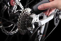 Bicycle gears and rear derailleur oiling. Studio shot on black background Stock Photo