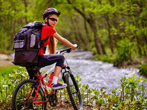 Bicycle girl with big rucksack cycling fording throught water . Stock Photos