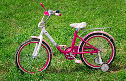 The bicycle for the girl on a green lawn. Stock Photo