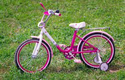 The bicycle for the girl on a green lawn. Stock Image