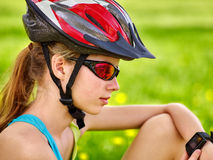 Bicycle girl looks on smart watch. Bicyclist girl watch on smart watch. Girl counts pulse after bicycle training. Bicyclist sitting on green grass Royalty Free Stock Image