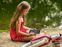 Bicycle girl into park. Children watch tablet pc. Stock Photo