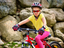 Bicycle girl into park rides in mountains. Stock Photos