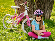 Bicycle girl wearing helmet read book on rest near . Stock Photo