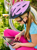Bicycle girl wearing helmet watching at tablet pc in cycling. Royalty Free Stock Images