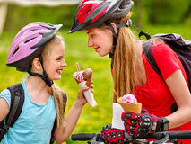 Bicycle girls cycling eating ice cream cone in park. Royalty Free Stock Images