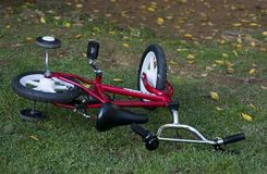 Bicycle on grass. Red kids bicycle on the grass with leaves royalty free stock photo