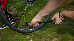 Young man`s hands pumping air into bicycle tyre using hand pump - image royalty free stock image