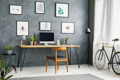 Bicycle in a grey home office interior with a wooden desk and ch