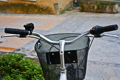 A bicycle handlebar with basket in a colorful street Royalty Free Stock Image