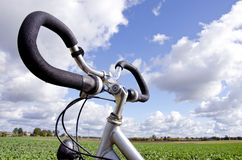 Bicycle handlebar on cloudy sky. No fuel needed. Bicycle handlebar closeup on background of blue cloudy sky. Vehicle does not require fuel. Active healthy people stock images