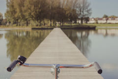 Bicycle Handlebars on a Lake Pier. Bicycle handlebars on a wooden pier looking to distance Royalty Free Stock Images