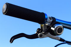 Bicycle handlebars. Modern black bicycle handlebars for exercise against blue sky Stock Photography
