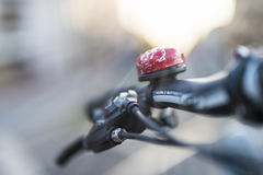 Bicycle handlebars. With red bell backlit by the sun Royalty Free Stock Images