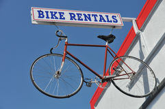 Bicycle hanges from a Bike Rentals sign outside. Bike rental sign with a bike haning from it next to a building Royalty Free Stock Photography