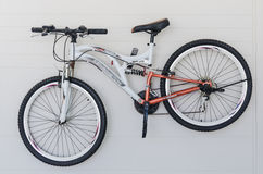 Bicycle hanging on white wall Stock Photo