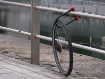 Bicycle stolen, leaving only a wheel, still locked to metal railing. royalty free stock photo