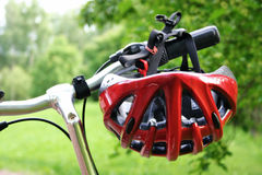 Bicycle helmet. Red bicycle helmet hanging from bicycle, green nature background Royalty Free Stock Image