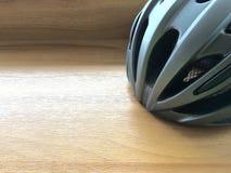Bicycle helmet. Grey bicycle helmet on wood table Royalty Free Stock Images