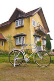 Bicycle home. White bicycle on the grass, the yellow house Royalty Free Stock Photos