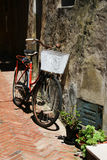 Bicycle infront of house. Red bicycle infront of house in europe Stock Photography