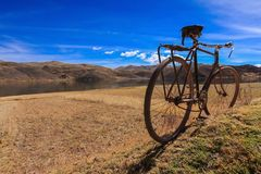 Bicycle journey;old fashion bicycle with the mountain range. Bicycle journey;old fashion bicycle parks on brown grass with the mountain range,lake and blue sky Royalty Free Stock Photography