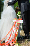 Bicycle with just married sign. Groom and bride on white bicycle with just married sign and colorful ribbons. Outdoors. Loving couple embracing in the background Stock Photography