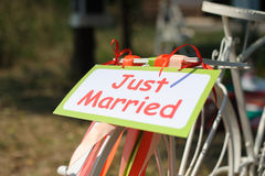 Bicycle with just married sign. White bicycle with just married sign and colorful ribbons. Outdoors Royalty Free Stock Image