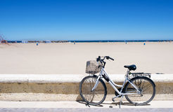 Bicycle in La Malvarrosa beach, Valencia, Spain. A bicycle parked in the seafront of the popular La Malvarrosa beach, in Valencia, Spain Royalty Free Stock Images