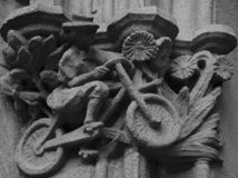 Bicycle lady with flowers on the capital. Shot in black and white detail of the sculpture on the facade of this historic building representing some characters / royalty free stock photo