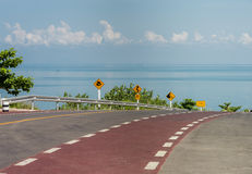 Bicycle lane on curve road along the beach with Traffic sign. Bicycle lane on curve road stock images