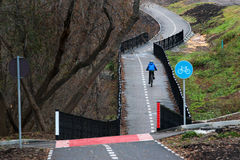 Bicycle lane in late autumn. Lone biker riding over small bridge Royalty Free Stock Photography