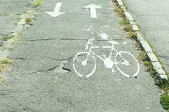 Bicycle lane on old asphalt with sign and arrows. Bicycle lane on old asphalt with bicycle sign and arrows Stock Photos