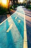 Bicycle lane in a park. Bicycle or bike lane receding through a park at sunset Stock Photo