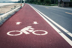 Bicycle lane or path, icon symbol on red asphalt road Royalty Free Stock Photography