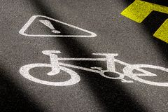 Bicycle lane sign on asphalt road. Concept of biking safety and active lifestyle. 3D perspective view at night time with. Headlights beams royalty free stock images