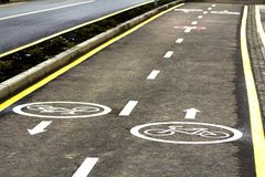 Bicycle lane signs on the asphalt road surface.  Royalty Free Stock Photos