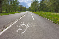 Bicycle lane with white bicycle sign at town park Royalty Free Stock Photos