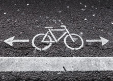 Bicycle lane. White road marking with arrows. On dark asphalt Royalty Free Stock Photography